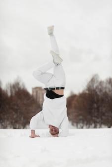 Intérprete de hip hop masculino de pie sobre la cabeza mientras está en la nieve.