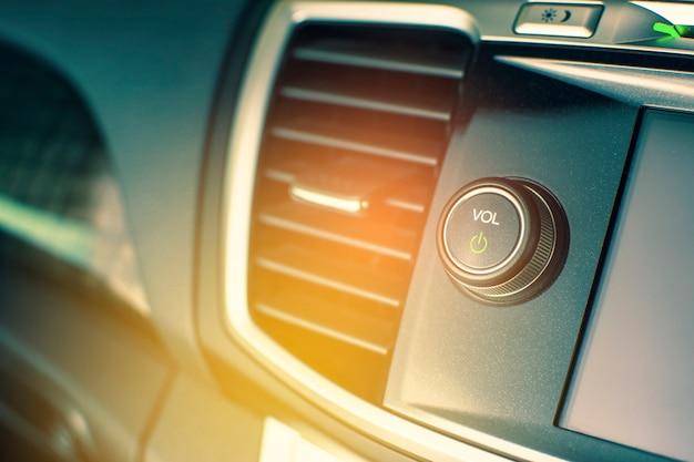 Interruptor de control del botón de encendido de la unidad principal de audio multimedia en automóviles de lujo, concepto de pieza automotriz.