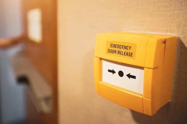 Interruptor de emergencia de primer plano para abrepuertas en la salida de incendios del edificio.