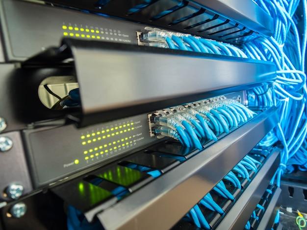 Interruptor de red y cables de ethernet en gabinete de rack