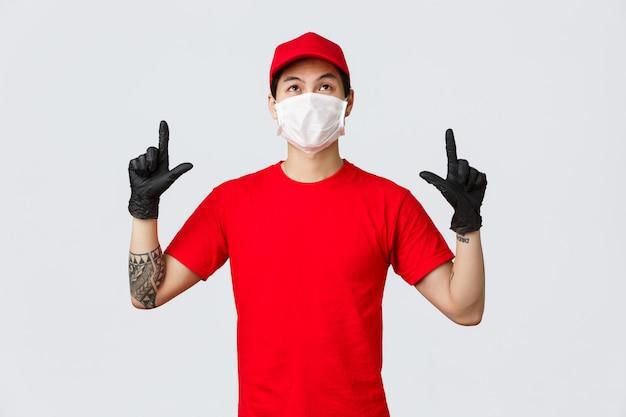 Intrigado lindo repartidor asiático con tatuaje, con gorra de uniforme y camiseta roja, apuntando con los dedos hacia arriba, mirando el anuncio superior con interés, leyendo el cartel hacia arriba. courier promueve el servicio de la empresa