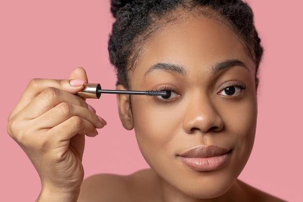 Inventar. mujer de piel oscura haciendo maquillaje y mirando involucrado