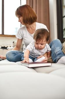 Inventiva madre moderna con hijos multitarea en la mañana. mamá y bebé son tecnologías y aparatos modernos. trabajar en casa en el desvío.