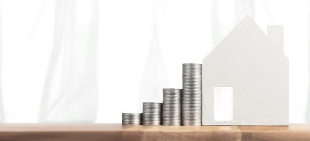 Inversión inmobiliaria y casa hipoteca concepto financiero pila de monedas de dinero. casa de negocios