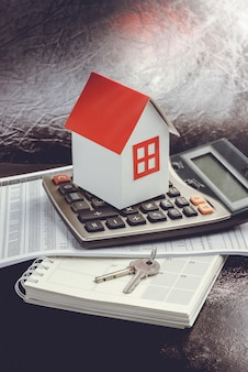 Inversión inmobiliaria. casa, llave y calculadora en mesa.