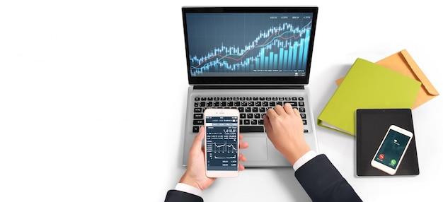 Inversionista que analiza el mercado de valores financiero. teléfono inteligente en la mano y pantallas de computadora