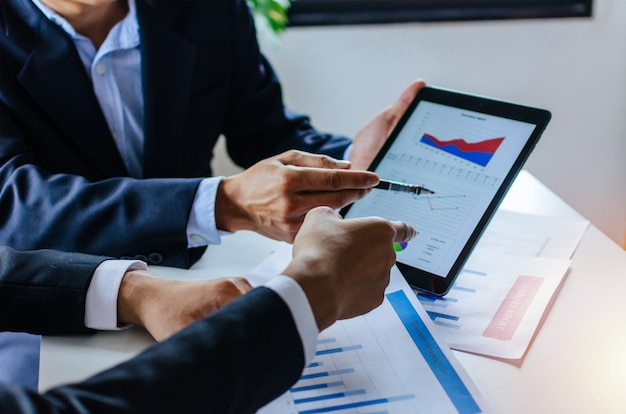 Inversor de hombre de negocios de dos socios hablando de información de gráfico de estadísticas financieras