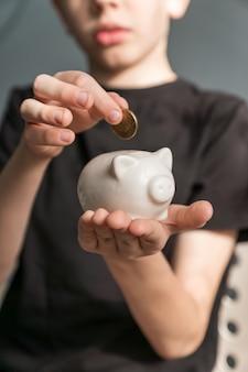 Inversor de niño pequeño poniendo una moneda en la hucha. ahorrando dinero para el concepto de educación futura.