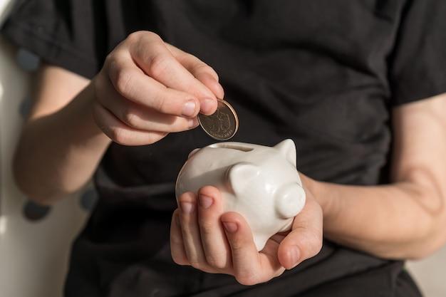 Inversor de niño pequeño poniendo una moneda en la hucha. concepto financiero interior.