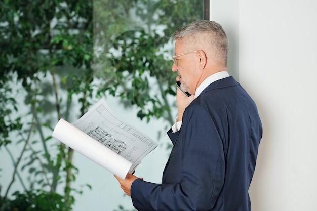 Inversor senior que comprueba el plano del edificio cuando habla por teléfono con su asistente o socio comercial