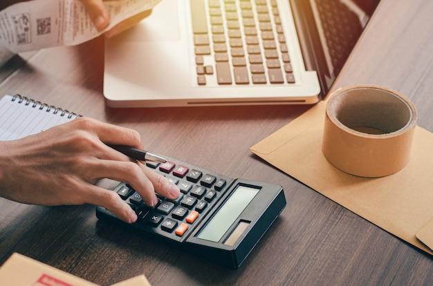 Los inversores masculinos están calculando estadísticas de costos de inversión con calculadoras y facturas gastadas.