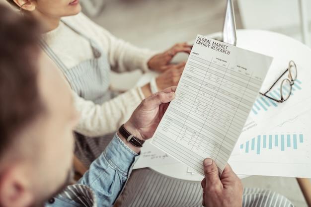 Investigación energética. dos socios comerciales sentados juntos en la mesa de café y mirando sus documentos sobre la investigación energética del mercado global.