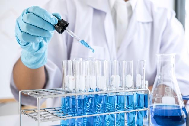 Investigación de laboratorio de bioquímica, científico o médico en bata de laboratorio con tubo de ensayo