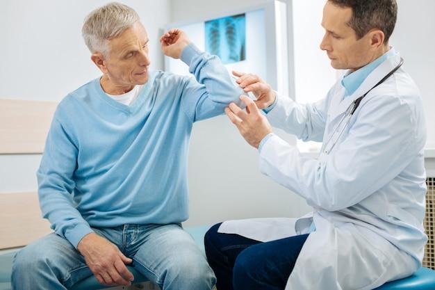 Investigación de problemas. agradable anciano positivo sosteniendo su brazo y dejando que el médico lo revise mientras se realiza un chequeo médico