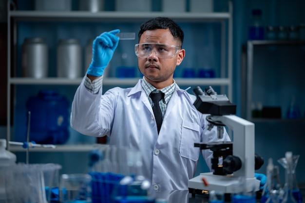 Investigación de tecnología de ciencia médica en laboratorio químico, científico profesional que trabaja para pruebas experimentales en medicina médica, trabajo con equipo de vidrio y líquido azul
