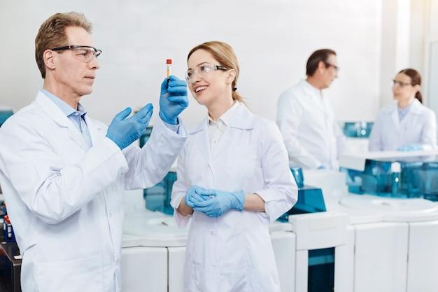 Investigador competente. joven mujer sonriente de pie frente a su colega manteniendo las manos juntas mientras mira a un lado