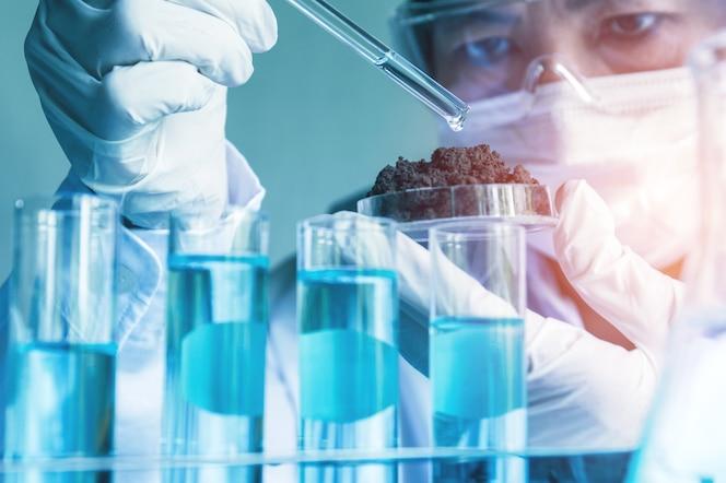 Investigador con tubos de ensayo químicos de laboratorio de vidrio con líquido