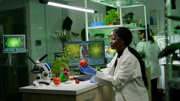 Investigador del equipo médico que trabaja en el laboratorio de farmacología examinando alimentos orgánicos