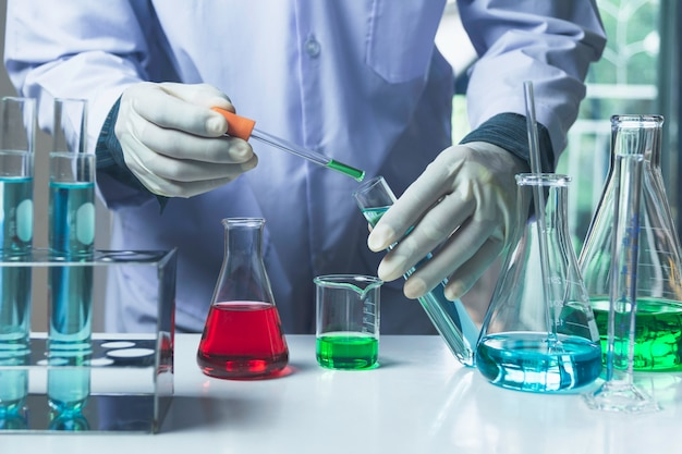 Investigador con laboratorio de vidrio, tubos de ensayo químico con líquido.