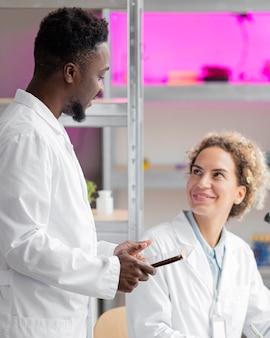 Investigador masculino y femenino conversando en el laboratorio