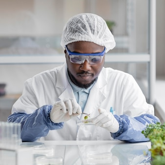 Investigador masculino en el laboratorio de biotecnología con placa de petri