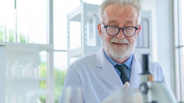 Investigador masculino senior piensa con concentración facial sobre la investigación científica en un laboratorio.
