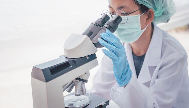Investigador médico femenino mirando un microscopio en un laboratorio médico. concepto experimental médico