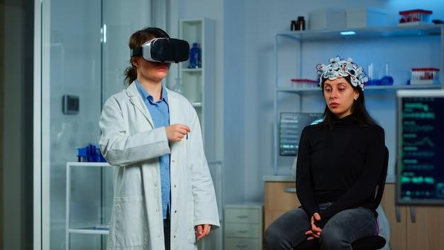 Investigador profesional con gafas de realidad virtual utilizando innovación médica en el laboratorio que analiza el escáner cerebral del paciente. equipo de médicos neurológicos que trabajan con equipo, dispositivo simulador de alta tecnología.
