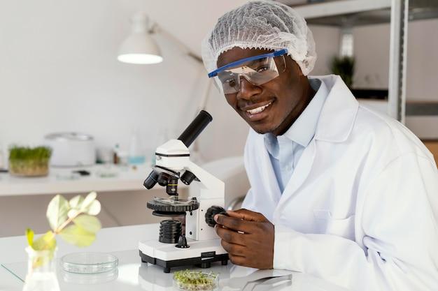 Investigador sonriente con microscopio