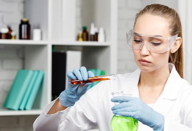 Investigadora con guantes y tubos de ensayo