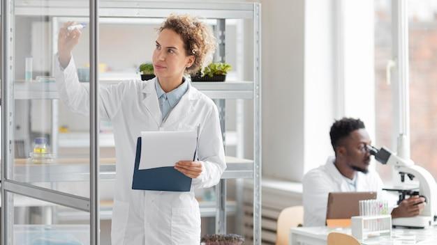 Investigadora con portapapeles en el laboratorio de biotecnología y colega masculino