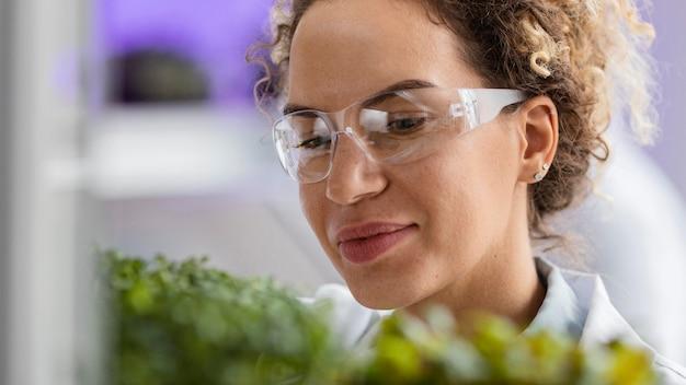 Investigadora sonriente en el laboratorio con gafas de seguridad y planta