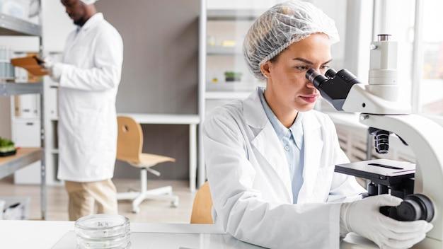 Investigadores en el laboratorio de biotecnología con tableta y microscopio