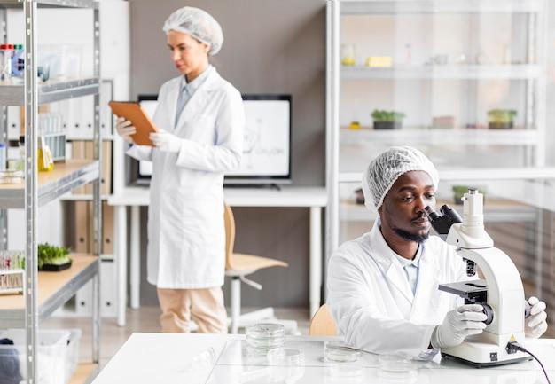Investigadores masculinos y femeninos en el laboratorio de biotecnología con microscopio y tableta