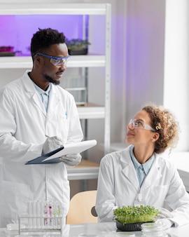 Investigadores sonrientes en el laboratorio comprobando la planta y escribiendo en el portapapeles