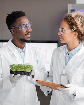 Investigadores sonrientes en el laboratorio con gafas de seguridad y planta