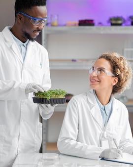 Investigadores sonrientes en el laboratorio con gafas de seguridad