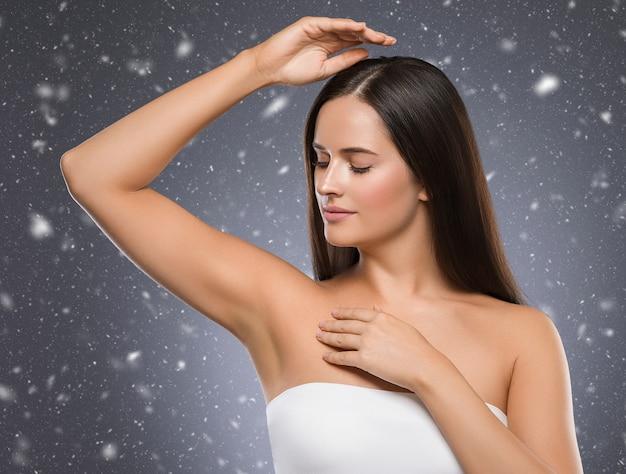Invierno axila mujer invierno concepto copos de nieve fondo mujer mano hasta depilación de belleza. tiro del estudio.