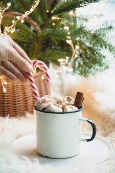 Invierno calentamiento taza de chocolate con malvavisco en el alféizar de la ventana.