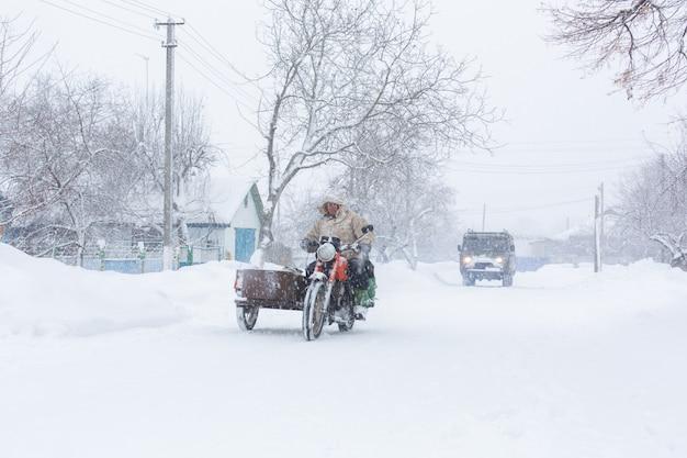 Invierno, las calles rurales están cubiertas de nieve, un hombre monta una motocicleta en una tormenta de nieve.