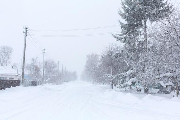En invierno, las calles rurales están cubiertas de nieve. tormenta de nieve