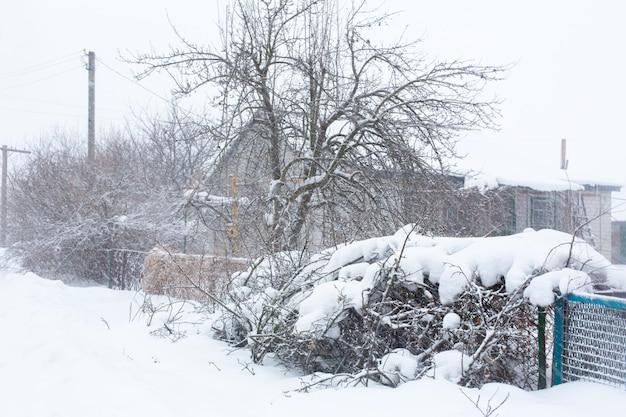 Invierno, las calles rurales están cubiertas de nieve, ventisca de nieve.
