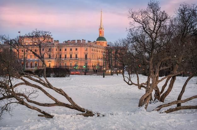 Invierno castillo mikhailovsky a través de los troncos retorcidos de los arbustos de lilas