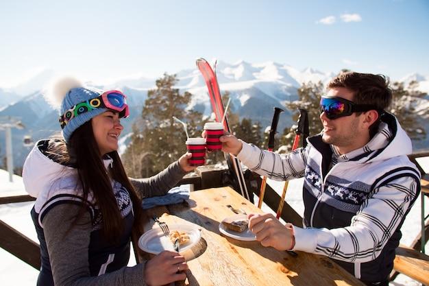 Invierno, esquiadores de esquí disfrutando del almuerzo en las montañas de invierno.