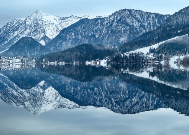 Invierno nublado lago alpino grundlsee (austria) con un fantástico patrón de reflexión sobre la superficie del agua.