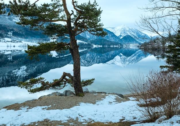 Invierno nublado vista del lago alpino grundlsee (austria) con un patrón fantástico de reflexión sobre la superficie del agua y un pino en la orilla.