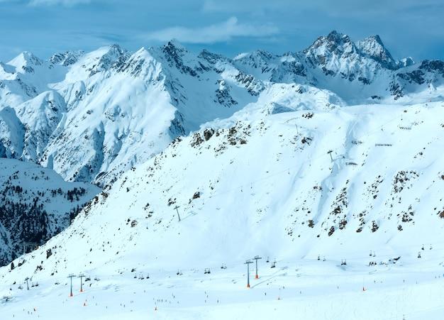 Invierno paisaje de los alpes silvretta y telesquí en pendiente, tirol, austria. todos los esquiadores son irreconocibles.