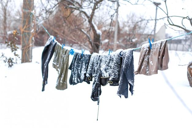 Invierno. la ropa se está secando en la calle. la ropa cubierta de nieve se seca sobre una cuerda tensada.