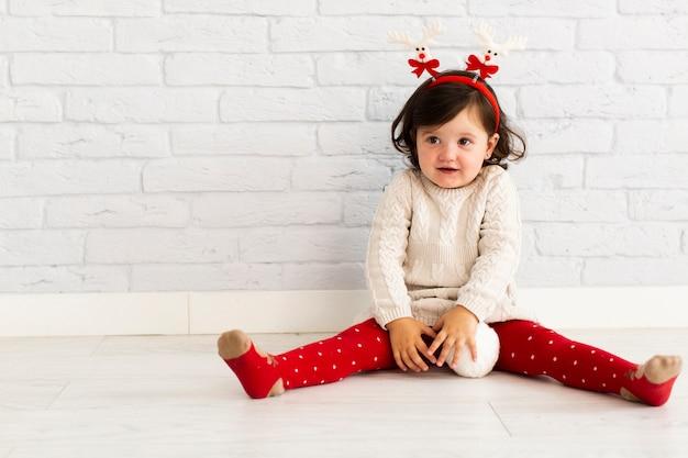 Invierno vestido niña jugando con bolas de nieve