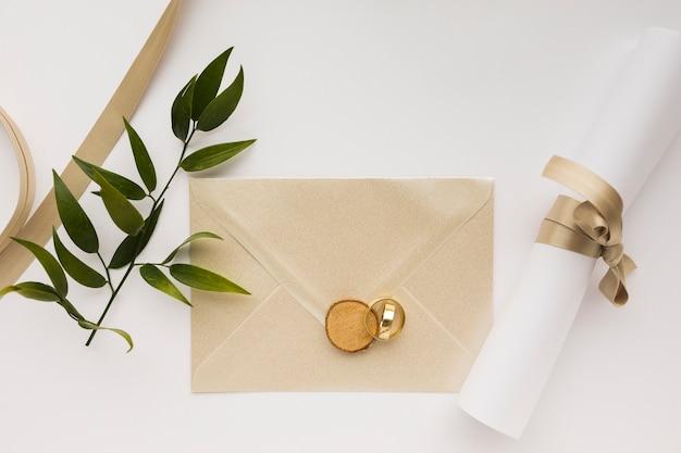 Invitación de boda y anillos de compromiso en la mesa